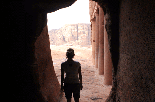 Inside a chamber looking out at the monuments of Petra.