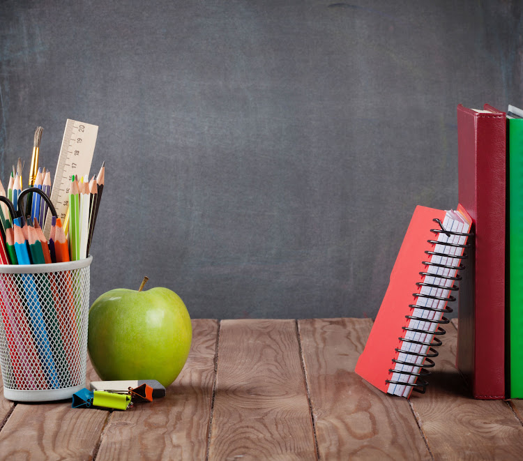 School supplies on classroom table in front of blackboard. File photo