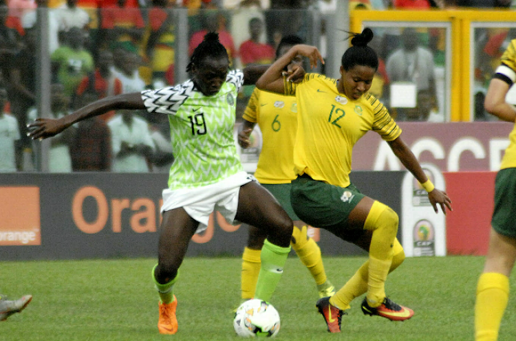 Nigeria's Ihezuo Chinwendu and Jermaine Seoposenwe, of SA, battle for possession during the Africa Women's Cup of Nations final in Accra, Ghana, on Saturday