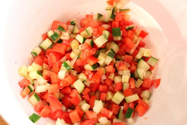In a medium size bowl, add the cucumber, tomato, onion, oil and vinegar as...