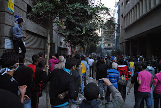 Photo: A crowd looks on at the site of clashes on Mohamad Mahmoud St. from a nearby side street