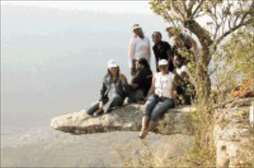 HAPPY HIKERS: The group sits in mid-air on Leopard Rock. © Sowetan.