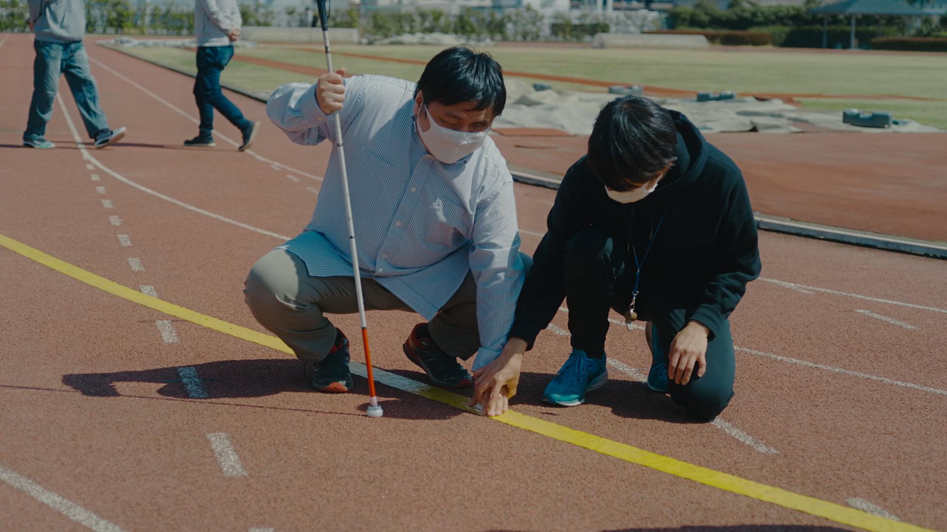 写真:コース上に貼られた黄色いガイドラインのテープに触れ、確認している男性のテスト走者。