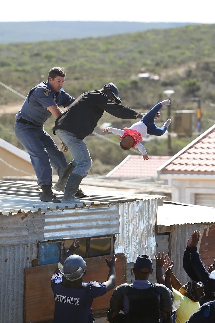 A Nelson Mandela Bay metro police officer grabs the father as he throws his child off the roof of a shack at the Joe Slovo informal settlement in Port Elizabeth on 12 April 2018.
