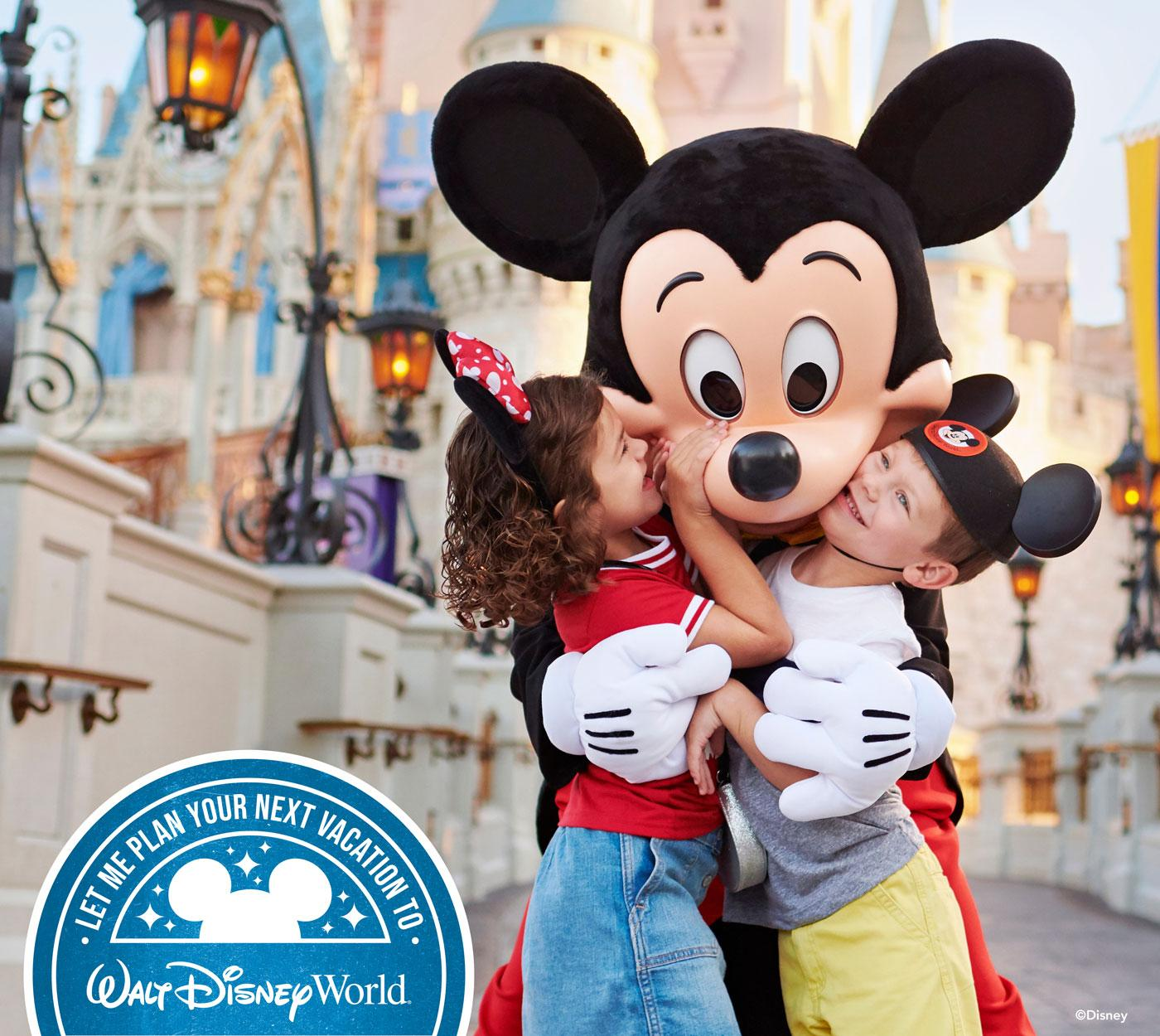 two smiling children wearing mickey mouse ears are hugged by Mickey Mouse in front of the Disney castle at Walt Disney World.