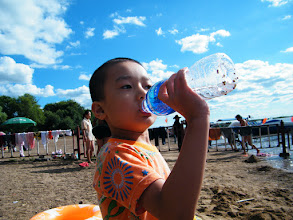 Photo: baby drink bottled water before join the river.