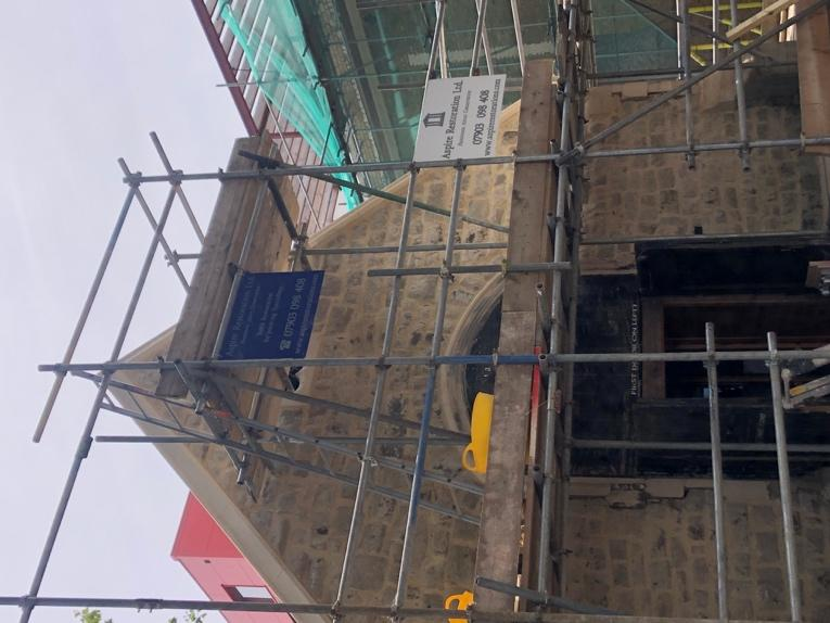 A scaffolding in front of a building  Description automatically generated