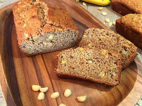 Sliced Banana Bread On A Wood Cutting Board With A Few Macadamia Nuts.