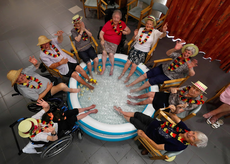 Residents at the Ter Biest house for the elderly refresh their feet in a pool on a hot summer day in Grimbergen, Belgium.
