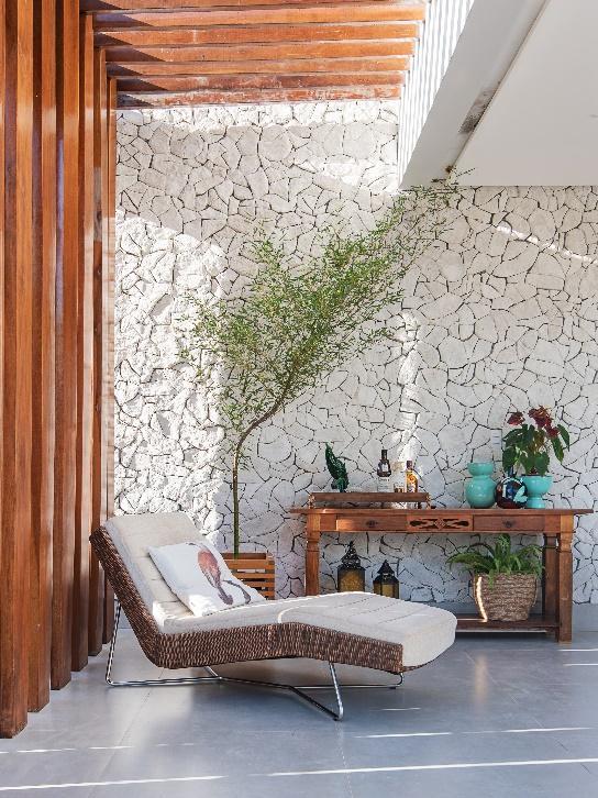 Área externa com parede principal revestida de pedras naturais, parede lateral com revestimento de madeira, piso de cimento queimado, espreguiçadeira de estofado branco e marrom e móvel de madeira com objetos decorativos
