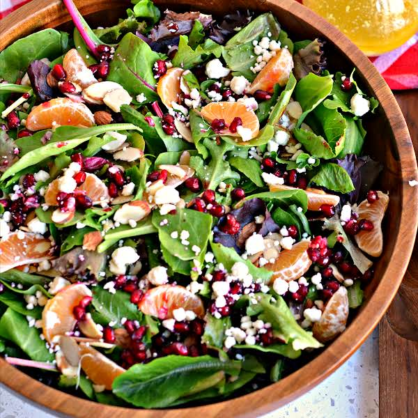 This Delectable Christmas Salad Brings Spring Greens Together With Sliced Almonds, Feta Cheese, Mandarin Oranges And Pomegranate Arils All Drizzled With A Tangy Honey Mustard Champagne Vinaigrette.