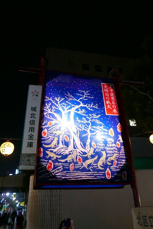 There is a famous piece of art by Utagawa Hiroshige during the 1797–1858 Edo period depicting this event showing the foxes (kitsune) gathering at a tree on New Year's Eve to pay homage at the Ōji Inari shrine, the headquarters of the Inari cult that centers on the god of the rice field, for whom the fox serves as messenger. On the way to Ōji, the foxes have set a number of kitsunebi (foxfires), which farmers count to predict the upcoming rice harvest. You may see versions of the art around the area like we did.
