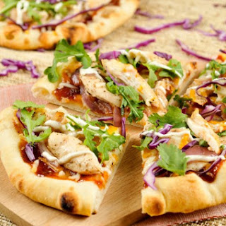 Wood-Fired BBQ Chicken Pizza with cheddar cheese, caramelized onions, and ranch drizzle
