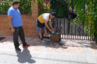 Photo: Itinerant knife grinder at work. He advertises his distinctive presence by blowing a scale on a plastic pan-pipe