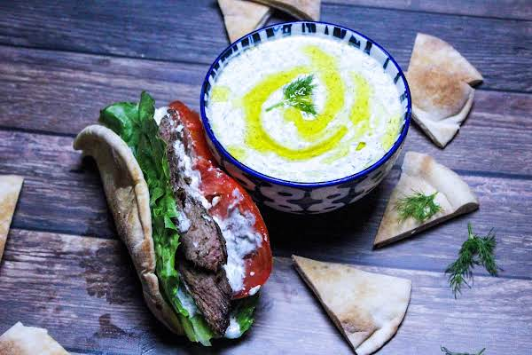 A Bowl Of Greek Tzatziki Alongside A Steak Sandwich Drizzled With Sauce.