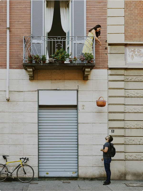 Mattia looks up as a customer lowers a basket from her balcony for her book delivery