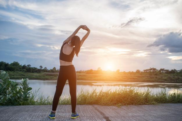 Healthy young woman warming up outdoors workout before training session at the park. Free Photo