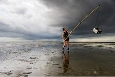 man met lange stok waaraan een bakje hangt op de vloedlijin