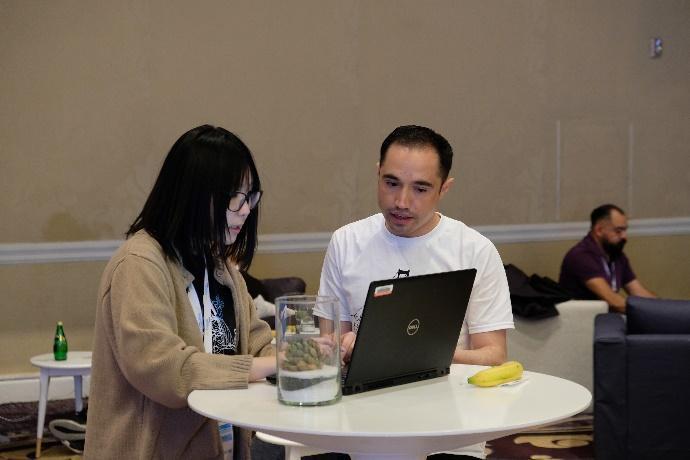 Obraz zawierający stół, osoba, ściana, siedzi  Opis wygenerowany automatycznie