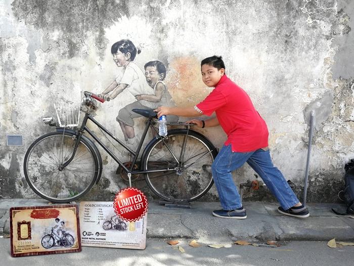 Bergambar lukisan dinding 'Kids on bicycle' dan gambar kecil adalah emas 0.5gram Public Gold.