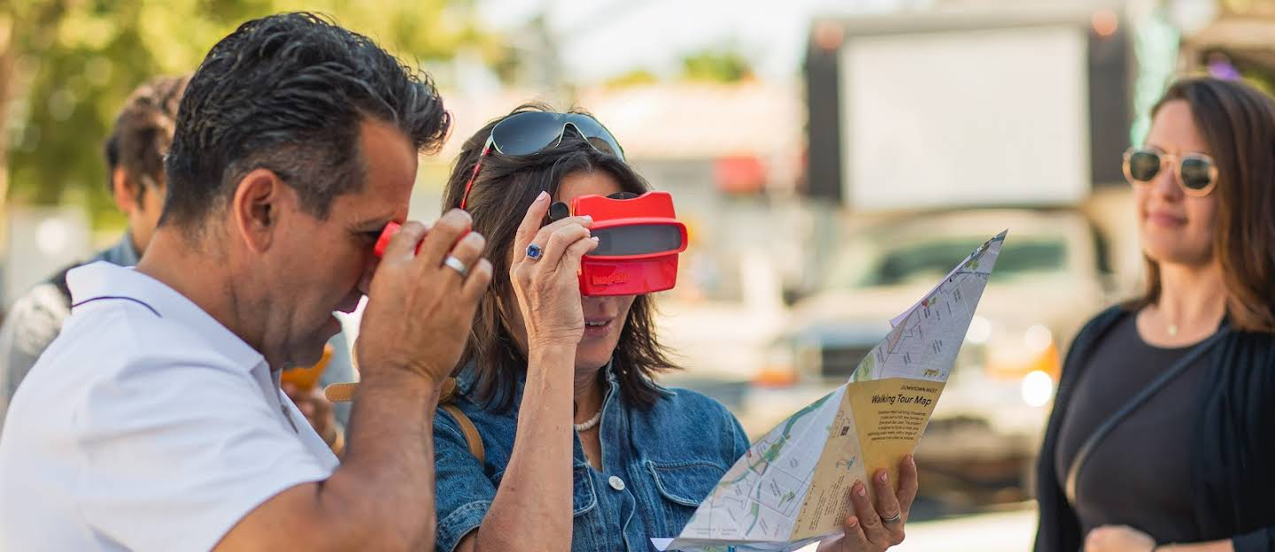 Two people looking at viewfinders and holding up a map of the project site. One person looking off into the distance.