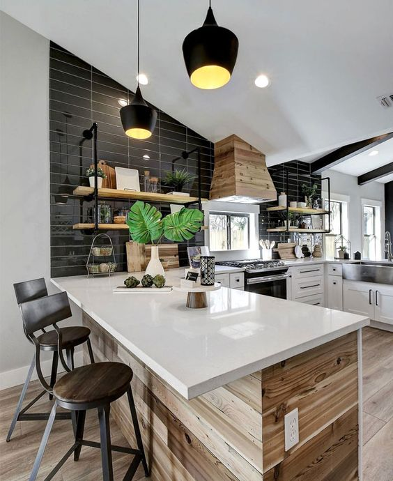 modern c-shaped kitchen with white marble countertops, wood paneling, black tile backsplash and a mix of different modern finishes