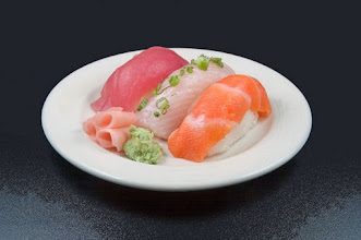 Photo: White plate of assorted sushi on dark background
