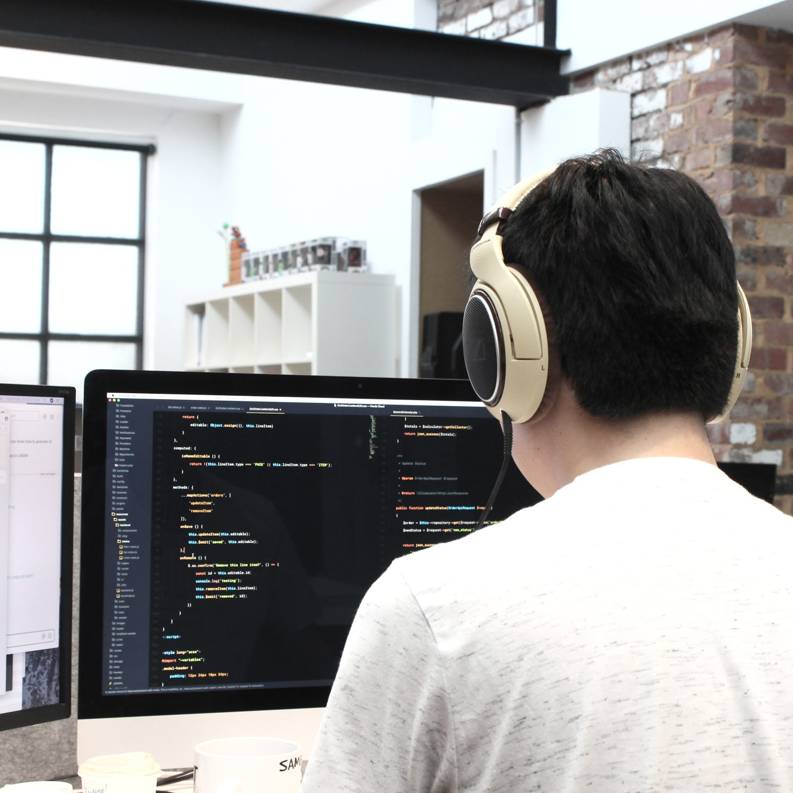 Man in white shirt wearing headphones and looking at computer monitor displaying code