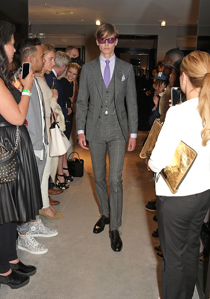 Guests including Lewis Hamilton, Paloma Faith and Labrinth look on as a model walks the runway at a cocktail reception celebrating the Tom Ford Spring/Summer 2016 collection during London Collections Men at the Tom Ford Sloane Street store