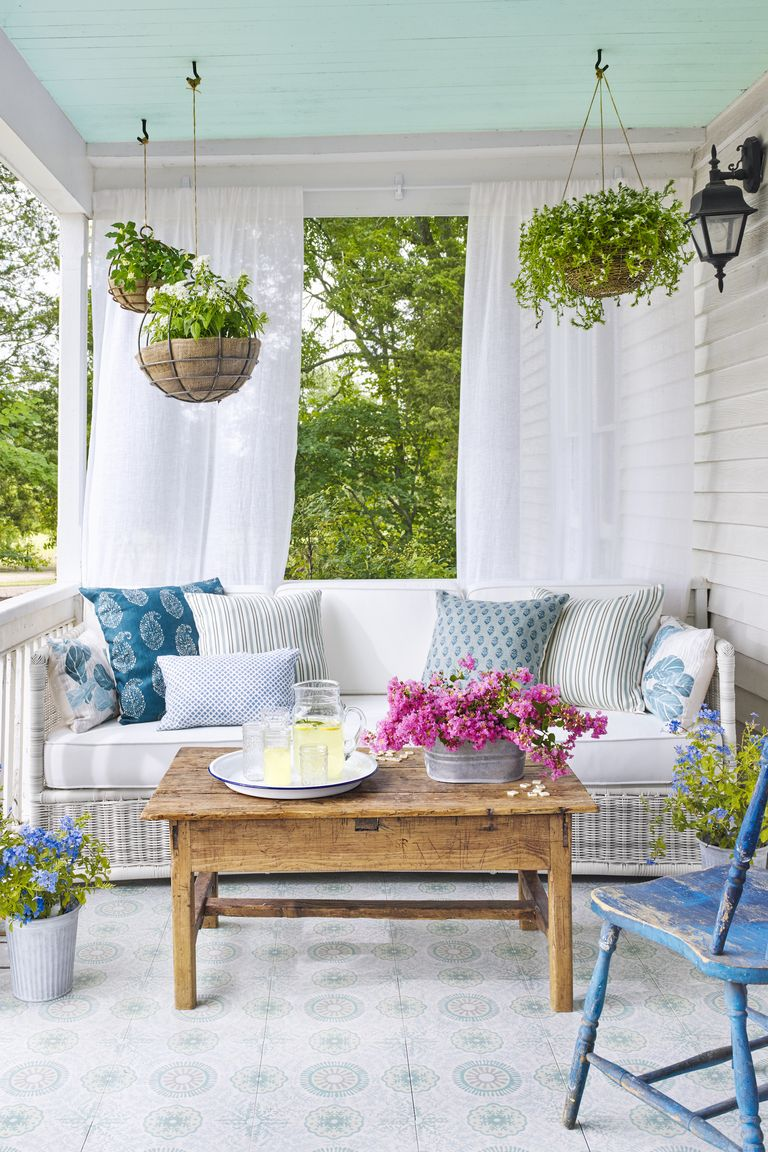 white couch on wrap around porch in summer with wooden table featured