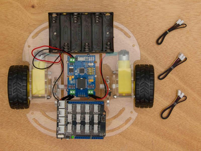 This is an image of the Wifi Robot's base with all pieces attached, and next to it are the three simple cables used to connect the Arduino.