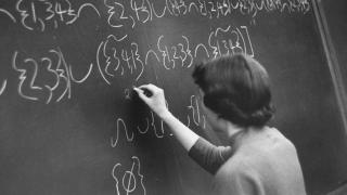 image of woman writing on chalkboard