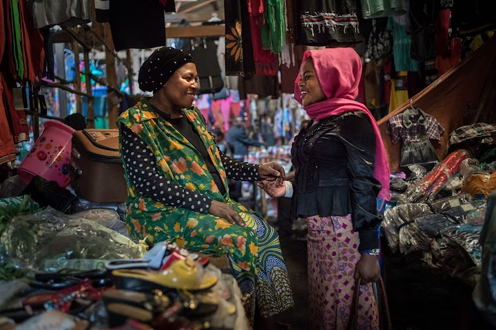 Djamila conversando com outra mulher em um mercado em Bukavu.