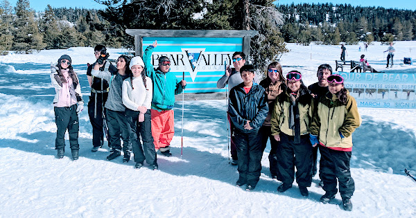Vista Voyagers staning in the snow in ther winter gear, posing for a photo in front of the Bear Valley sign