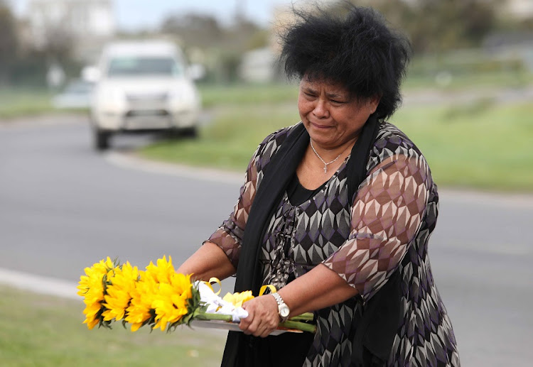 Jacoba Mouton who worked at Denel for 22 years lays flowers on Tuesday in front of the entrance of Rheinmetall Denel Munitions in Macassar where several employees were killed in an explosion. Picture: ESA ALEXANDER/SUNDAY TIMES