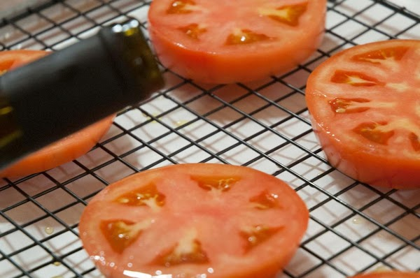 Drizzle a bit of olive oil over each tomato slice.