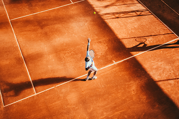 Birds-eye-view of tennis player poised to hit the tennis ball.
