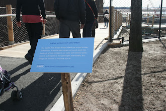 """Photo: Sign on the new bridge…  """"Is that a bounce in your step?  The Squibb Park Bridge design makes use of trail bridge technology. It is built with cables and wood, much like hundreds of trail bridges in our state and national parks.  Since it is designed to be lightweight and flexible, the bridge will bounce as you walk over it."""""""