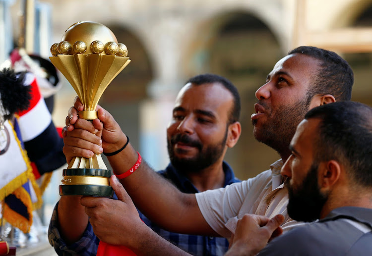 Customers hold a model of the Africa Cup of Nations' trophy at a shop in Al Ataba, Cairo