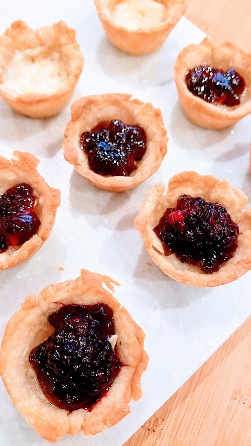 Berry Brie Bites, an easy recipe using only 4 ingredients, pie dough, brie, berry jam, and berry of your choice. Perfect for a party or potluck.