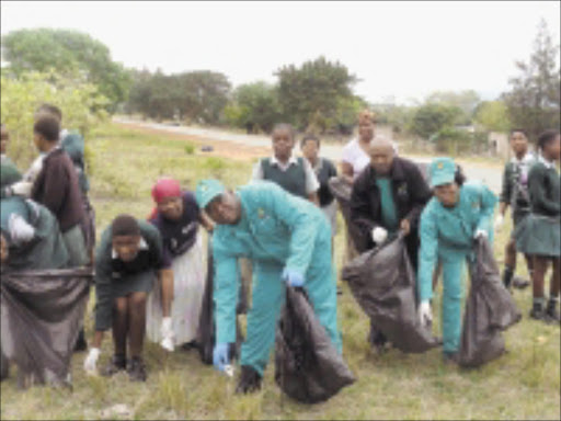 DIRT REMOVAL: Nkomazi mayor, Johan Mavuso, wearing blue gloves, picks up refuse with community members. Pic: Riot Hlatshwayo. 26/10/2009. © Sowetan.
