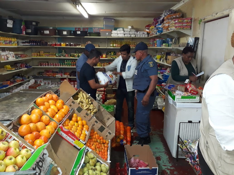 Police officials during the health safety raid in Cambridge spaza shops.