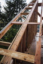 """Photo: We cut in 2x6 lookouts to hold the flyrafter.  It was braced square to the wall before lifting, then we install look outs as we go for overhangs this large (24"""")"""