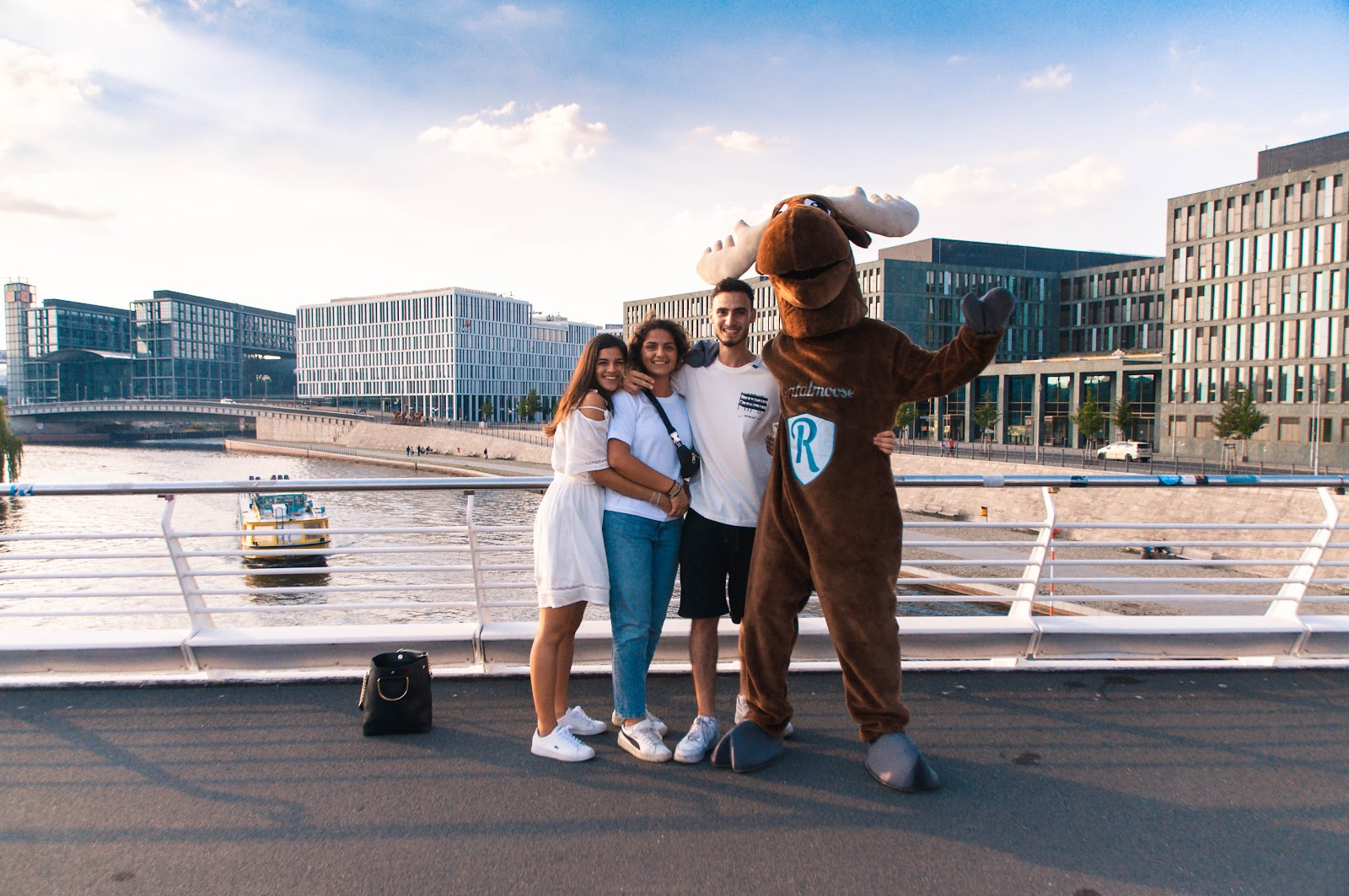 Rentalmoose Mascot posing with three tourists at Kronprinzenbruecke in downtown Berlin, Germany. Berlin Spree and modern office buildings in the background.