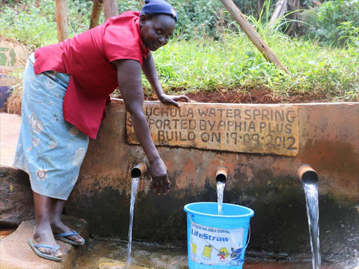A women in Muchula spring in Isalua village, Kakamega County fetching water.