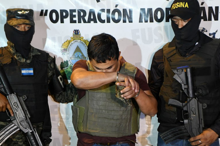 A file photo from a previous drug trafficking incident shows Members of the Honduran National Inter-Agency Security Force guard drug trafficking suspect Jeffrey Dario Guzman (C) in the Armando Escalon Air Force base in the town of La Lima, department of Cortes on November 9 2017