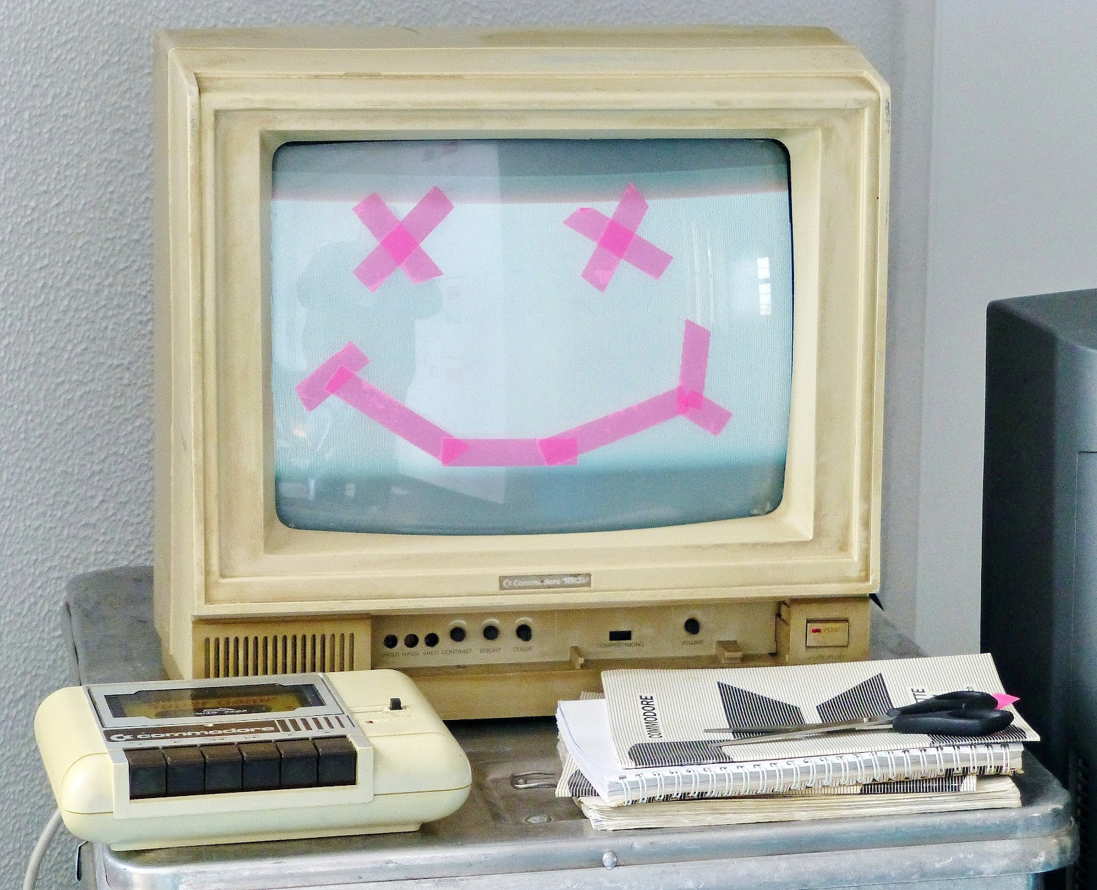 computer with smiley face taped on the screen
