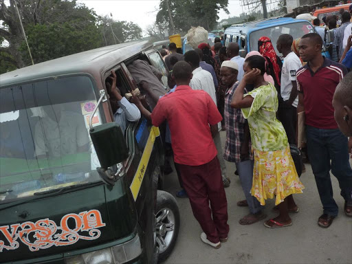 Commuters scuffle for matatus at a bus stage. /FILE