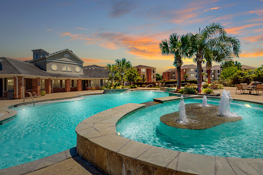 Reserve at Tranquility Lake's resort-style swimming pool with fountain at dusk