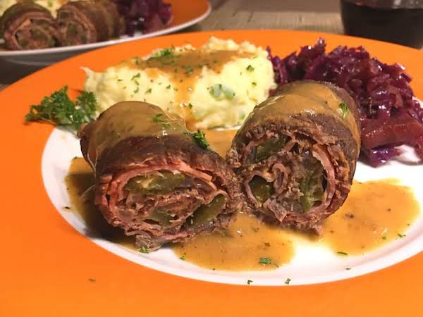 A Couple Beef Rouladen On A Plate With Mashed Potatoes And Red Cabbage.
